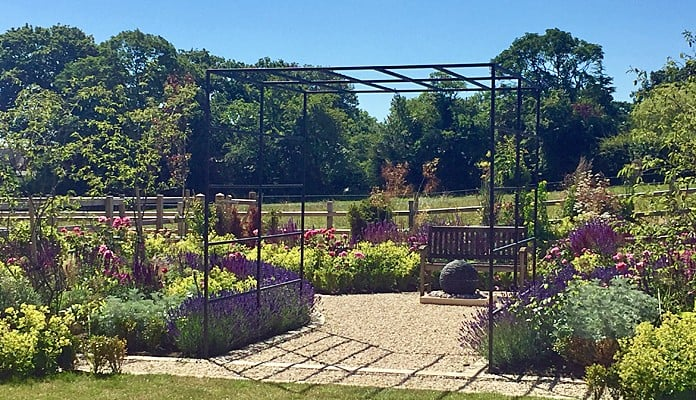 Daisy Barn Garden Square Pergola with seating area and water feature behind
